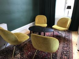 Ny inredning med gula sköna fotöljer blir fint tillsammans med handvävd orientalisk matta.
